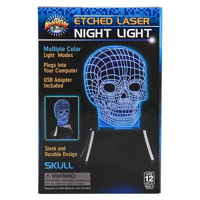 "Retail packaging for the Etched Laser Night Light. The night light is a standalone piece of glass etched into a skull design, sitting in a black base. When turned on, the etchings in the glass illustrate the skull design. The packaging advertises ""multiple colour light modes,"" ""plugs into your computer,"" ""USB adapter included"" and ""sleek and durable design"""