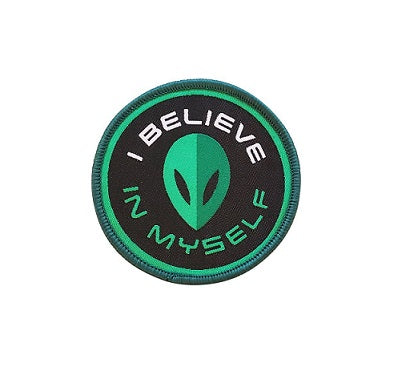 "A circular iron on patch that is black, white, and shades of green. The patch has an alien face in the centre with curved text around it that reads ""I believe in myself""."