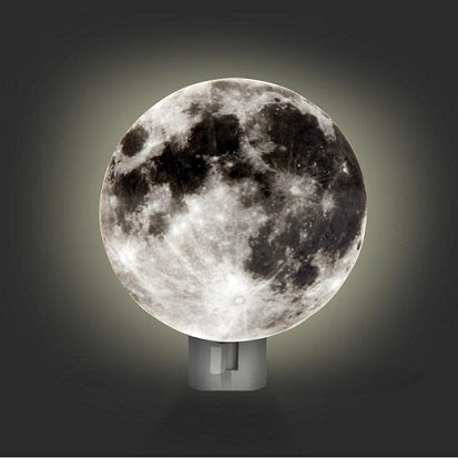 An image of the moon night light in a dark room. The night light is illuminated behind a circular cardboard image of the lunar surface to give the impression that the moon is glowing.