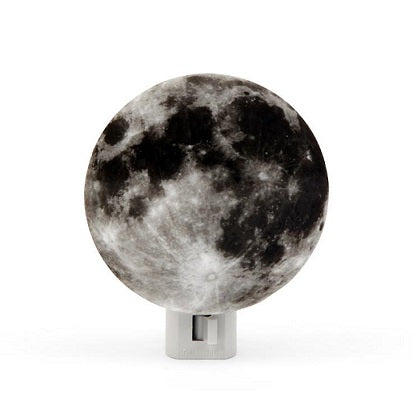 A moon night light. The night light has a circular cardboard cutout of the lunar surface in front of the night light bulb so that the moon will light up when the light is turned on.