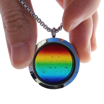 A silver necklace with a glass locket being held between two fingers. A light is being shone through the pendant to illustrate that the locket contains the full solar spectrum of light from the sun, which appears as a rainbow with small black lines