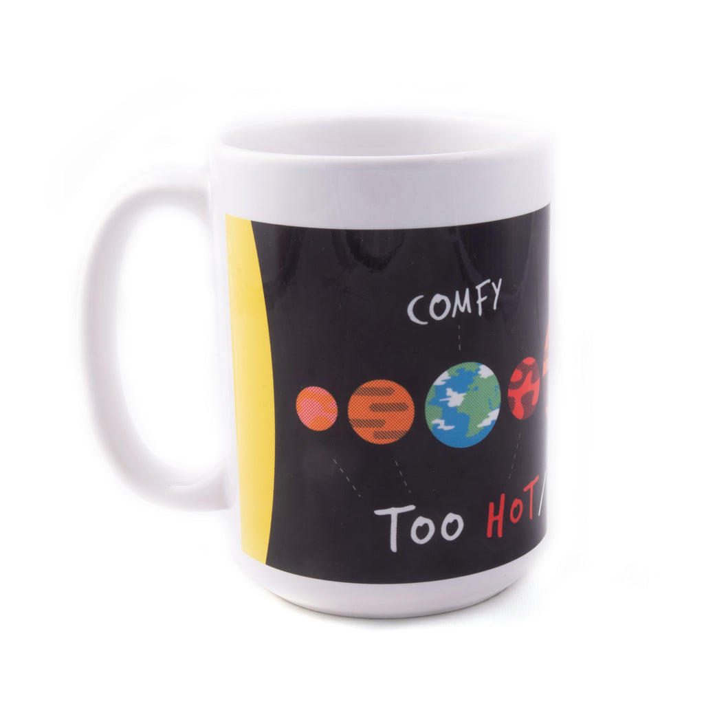 "A white ceramic mug with a printed cartoon graphic of the solar system. Text reads: ""Too hot/cold/toxic"" below different planets and ""Comfy"" above the Earth."