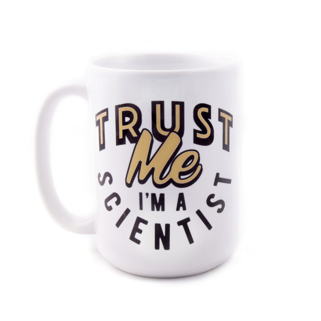 "A white ceramic mug with curved black and gold script that reads ""Trust Me, I'm A Scientist"""
