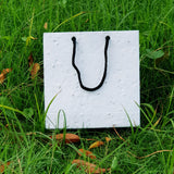 Plantable seed paper bags with black thread lying on grass