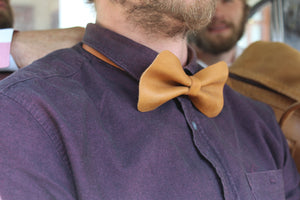 a photo showcasing the tan leather bow tie on a person