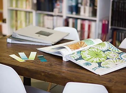 desk covered in design samples and inspiration