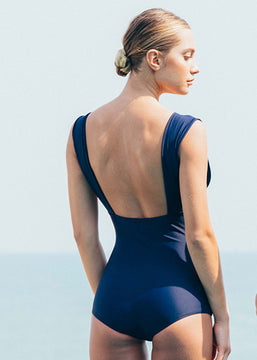 A woman from the back with a dark blue swimsuit.
