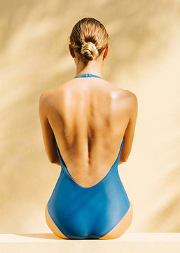 A woman from the back with a blue swimsuit.