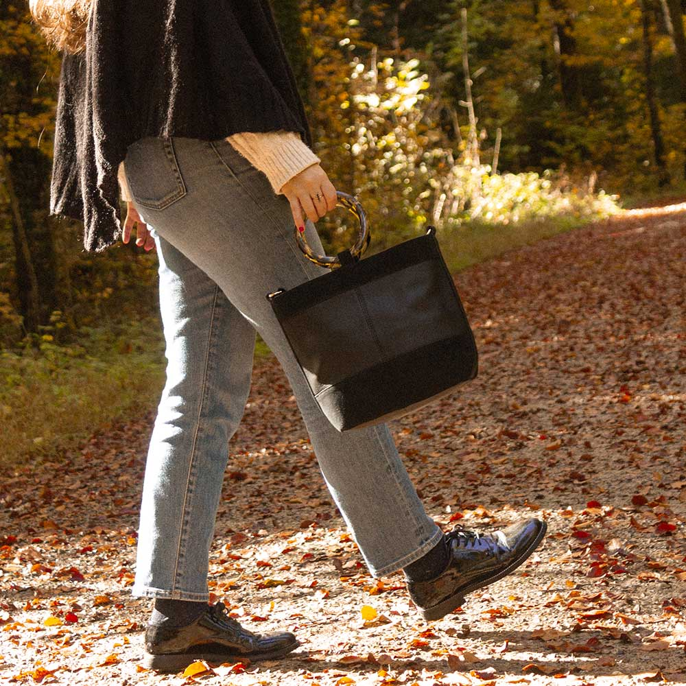 A woman walking in the forest with a black bag.