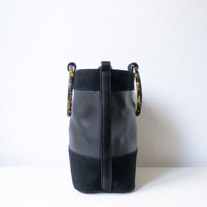 A black suede handbag from the left.