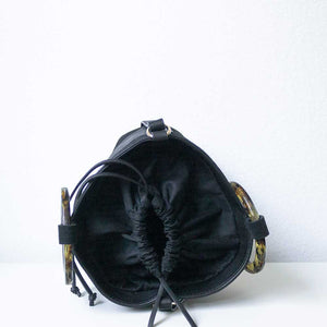 A black suede handbag open.