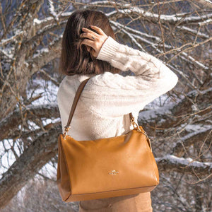 A woman wearing a camel shoulder bag.