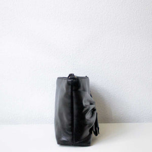A black leather bag from the right.