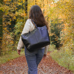 A woman walking in the forest with a black tote.