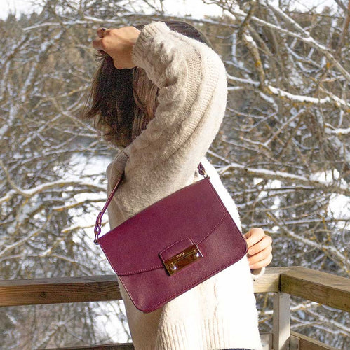 A woman wearing a bordeaux bag and a white pullover.