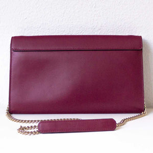 A bordeaux crossbody bag from the back.