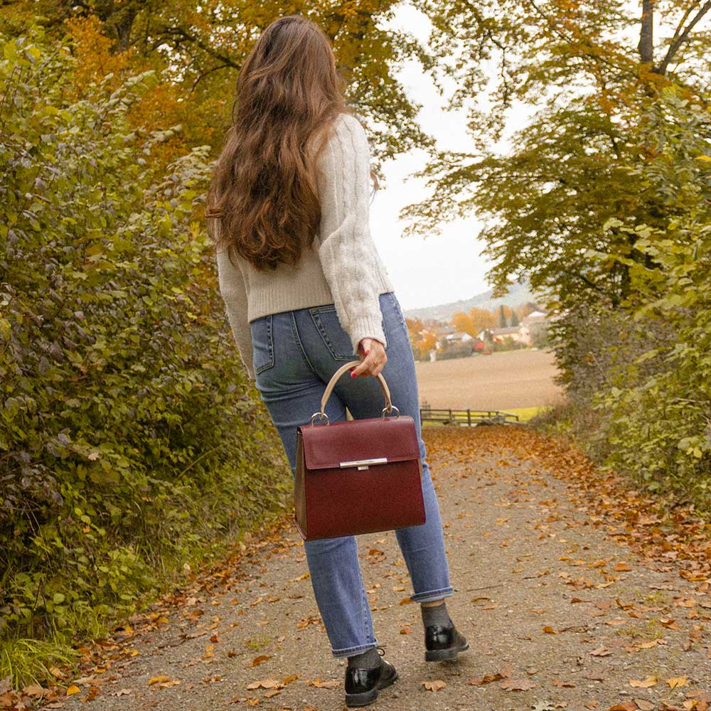 A woman wearing a bordeaux bag in the fall forest.