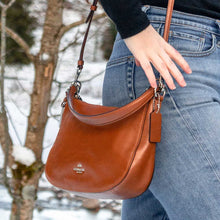 Charger l'image dans la galerie, A crossbody camel bag worn with jeans.