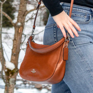 A crossbody camel bag worn with jeans.