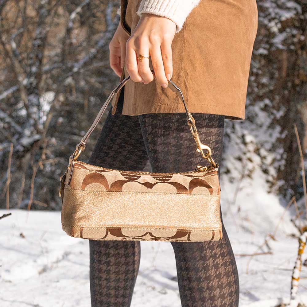 A woman walking in the snow with a monogram bag.