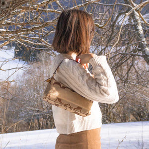 A woman with a white pullover and a golden bag.