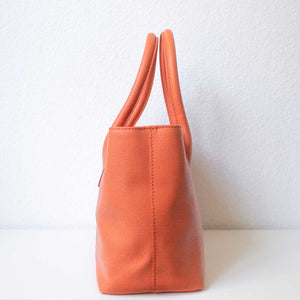 An orange handbag from the left.