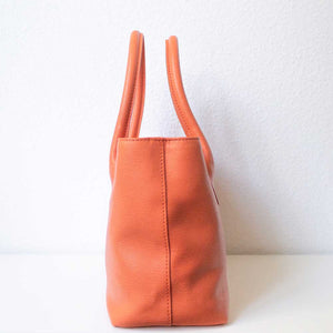 An orange handbag from the right.
