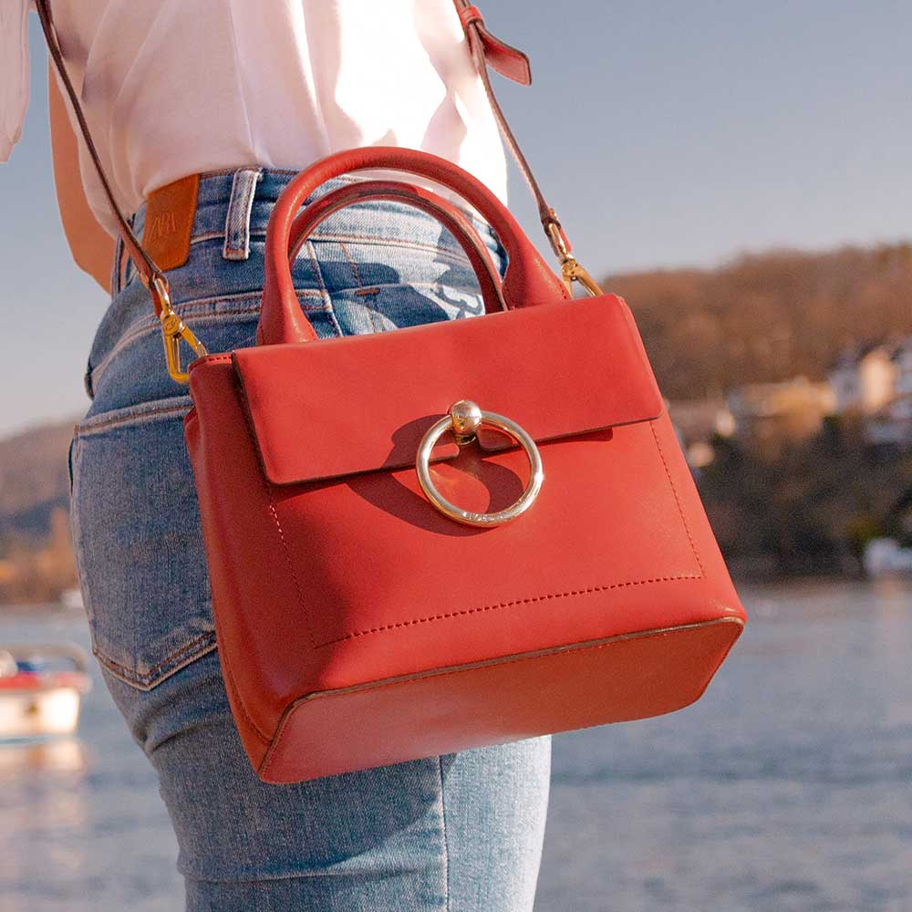 A red handbag worn with blue jeans.