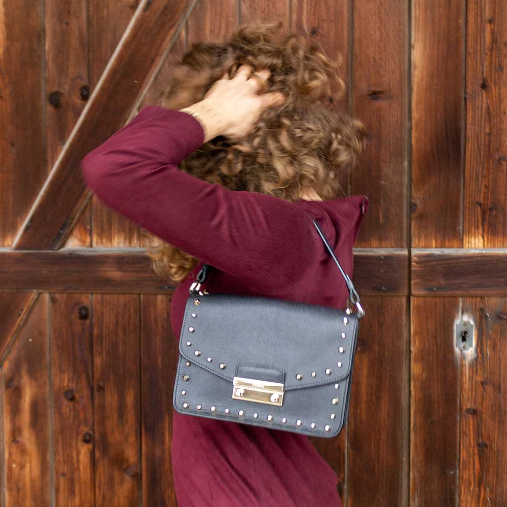 A woman doing her hair, wearing a black studded bag.