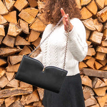 Charger l'image dans la galerie, A woman showing a black bag in front of chopped wood.