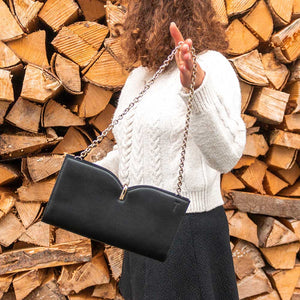 A woman showing a black bag in front of chopped wood.