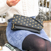 Charger l'image dans la galerie, A black pouch with golden eyelets worn with a blue skirt.