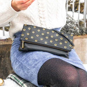 A black pouch with golden eyelets worn with a blue skirt.