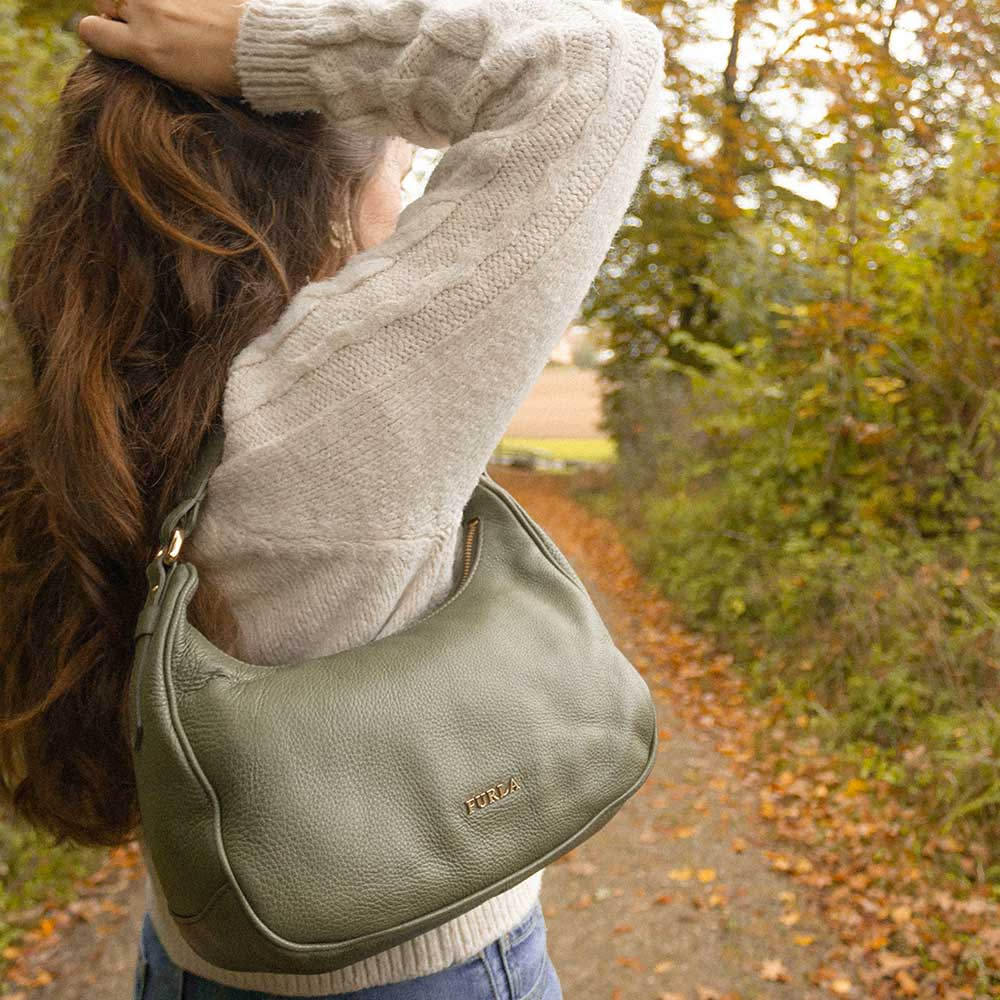 A woman attaching her hair, wearing a khaki handbag.