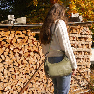 A woman standing in front of chopped wood.