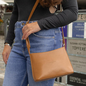 A woman wearing jeans and a camel bag.