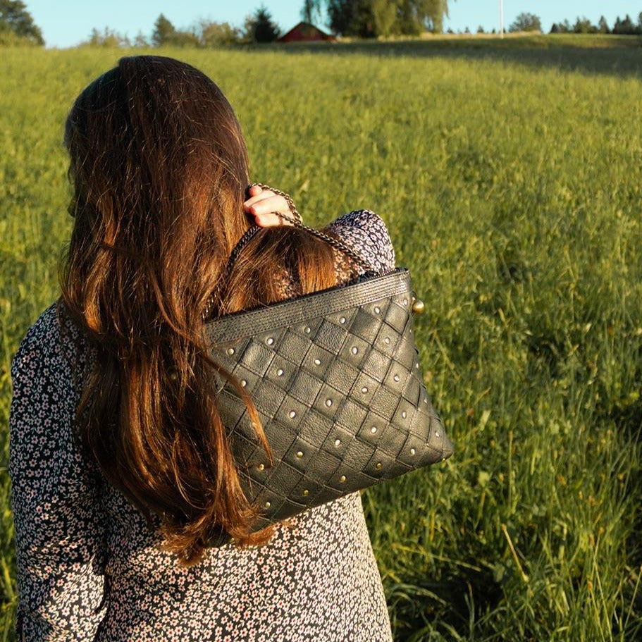 A woman in a field holding a black cross body bag.