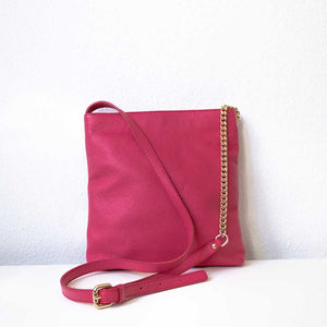 A raspberry crossbody bag from the back.