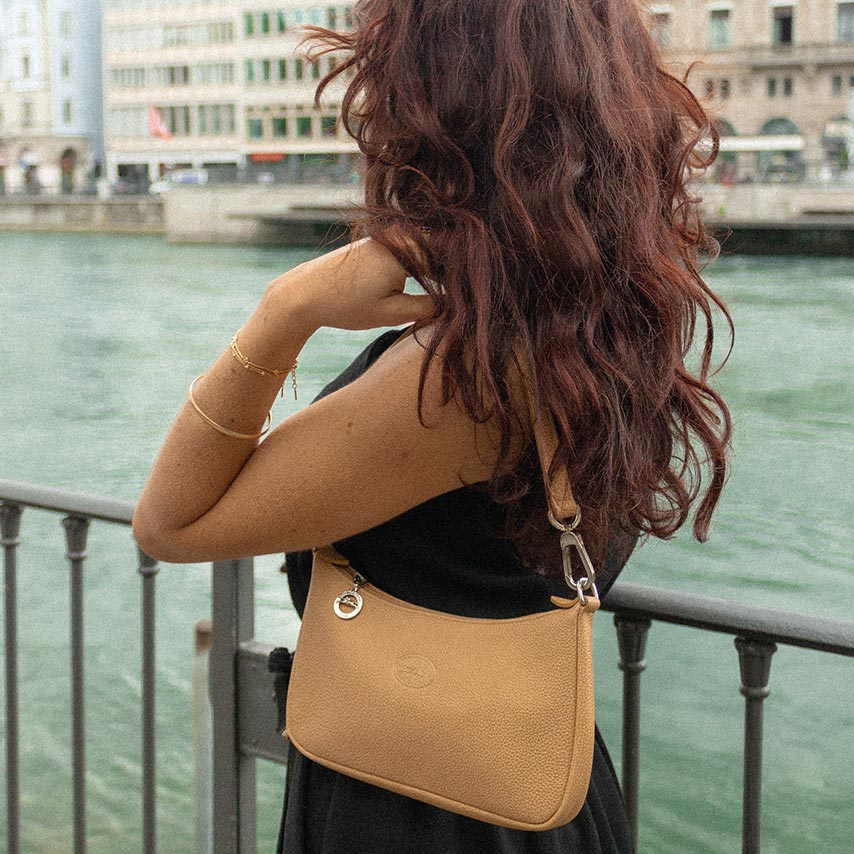 A woman with a camel baguette bag next to a river.