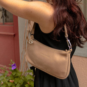 A woman wearing a black dress and beige baguette bag.