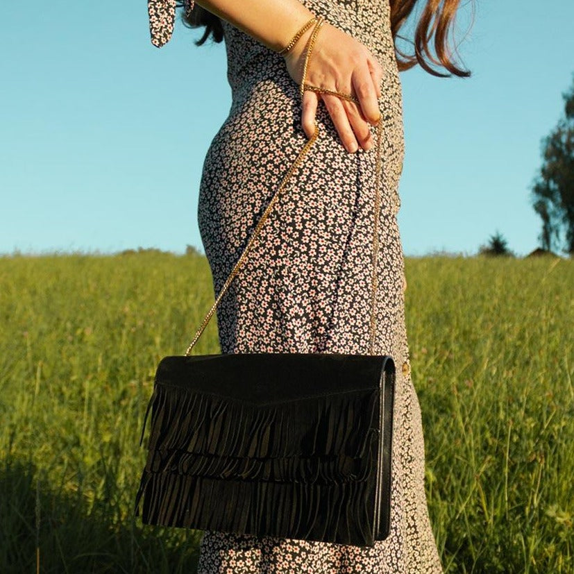 A fringes bag worn with a flower dress.