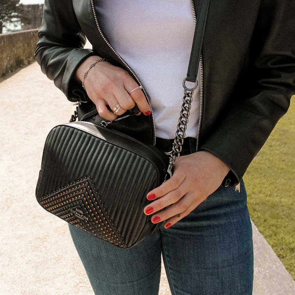 A woman wearing a leather black bag in a park.