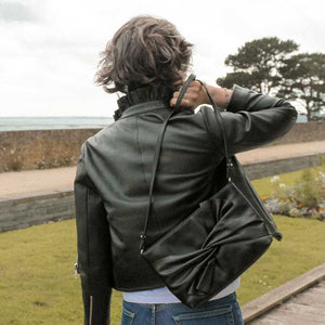 A woman wearing a leather bag and leather jacket.