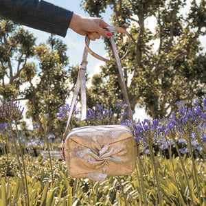 A rose gold cross body bag in a park.