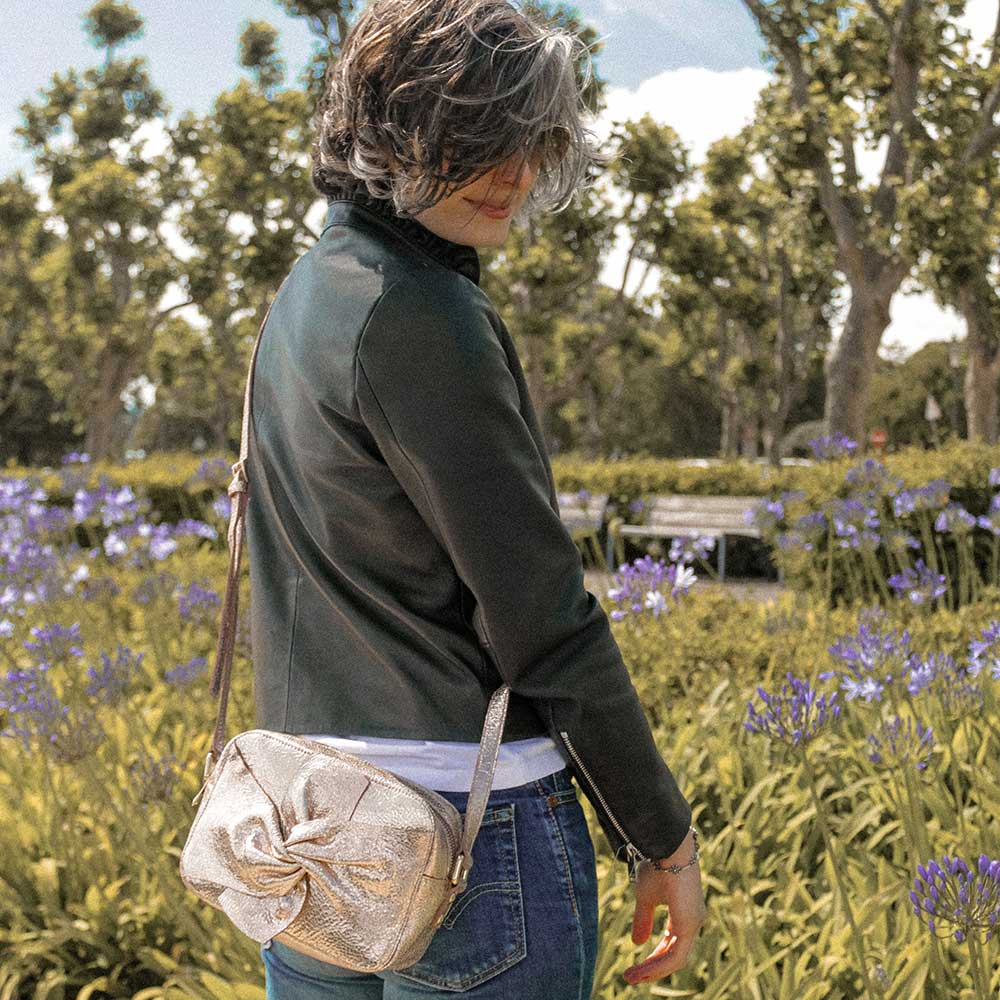 A woman in a park with a rose gold bag.
