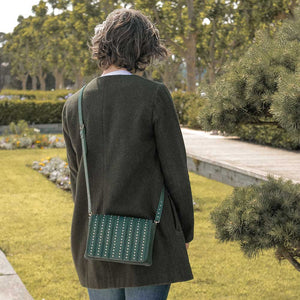 A woman in a park with a green crossbody bag.