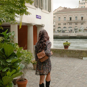 A woman walking in Zurich next to the river.