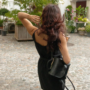 A woman wearing a black dress and backpack.