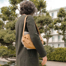 Charger l'image dans la galerie, A woman wearing a khaki coat and camel handbag.