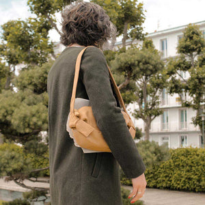 A woman wearing a khaki coat and camel handbag.